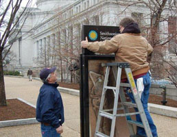 Putting up a post sign for a museum