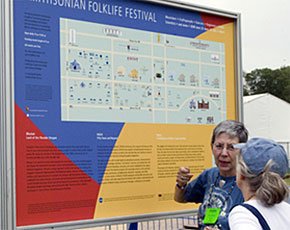 A volunteer with the 2008 Smithsonian Folklife Festival helps orient a visitor to the Mall. Photo by Joe Furgal, Smithsonian Institution.