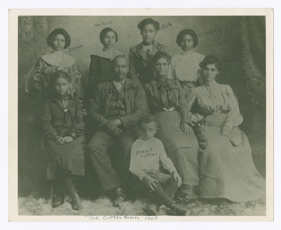 A black and white photograph of a family with a man and woman seated at the center. Six girls and one boy surround them.