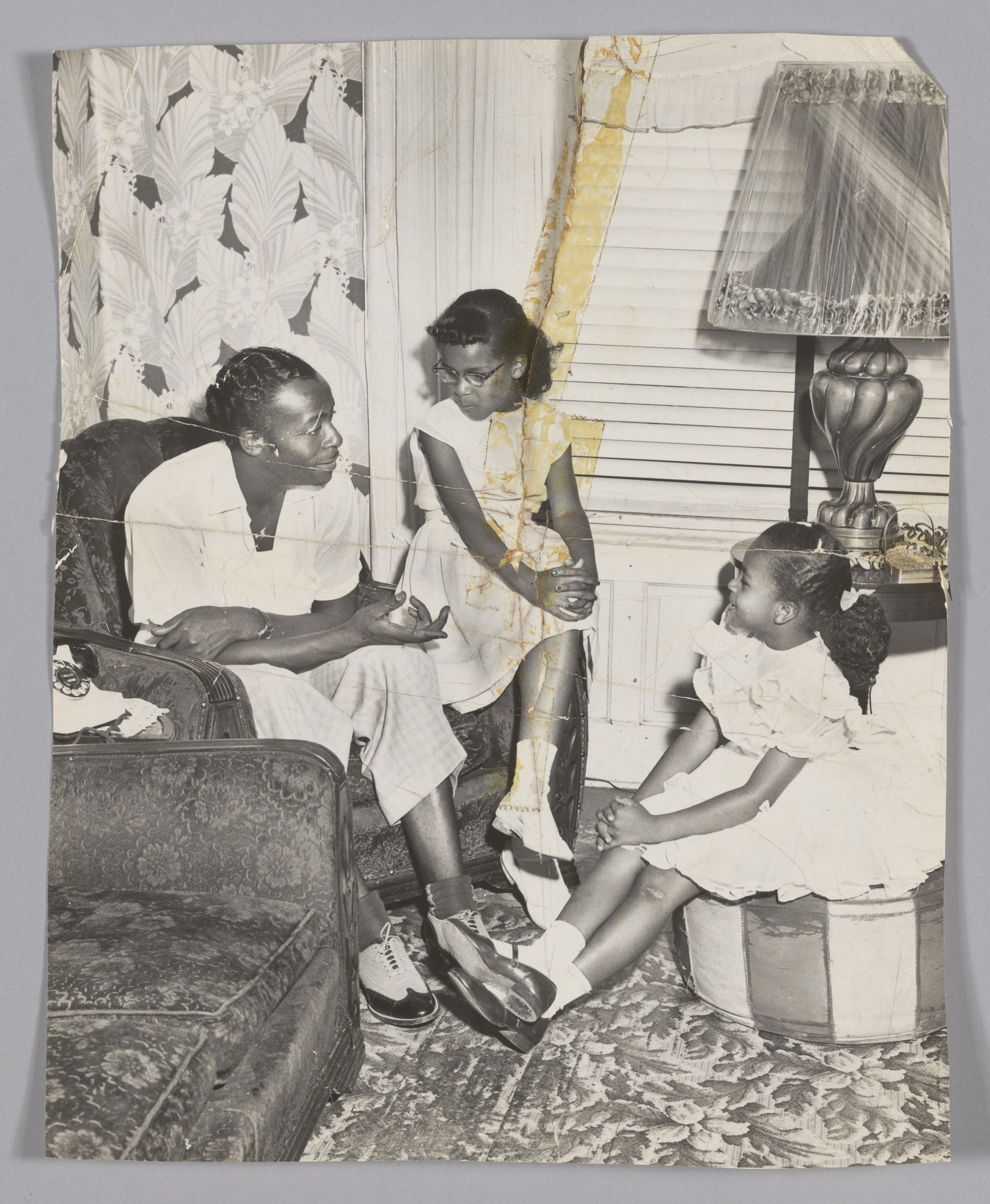 A man and two girls are seated in a living room. He is speaking to them.