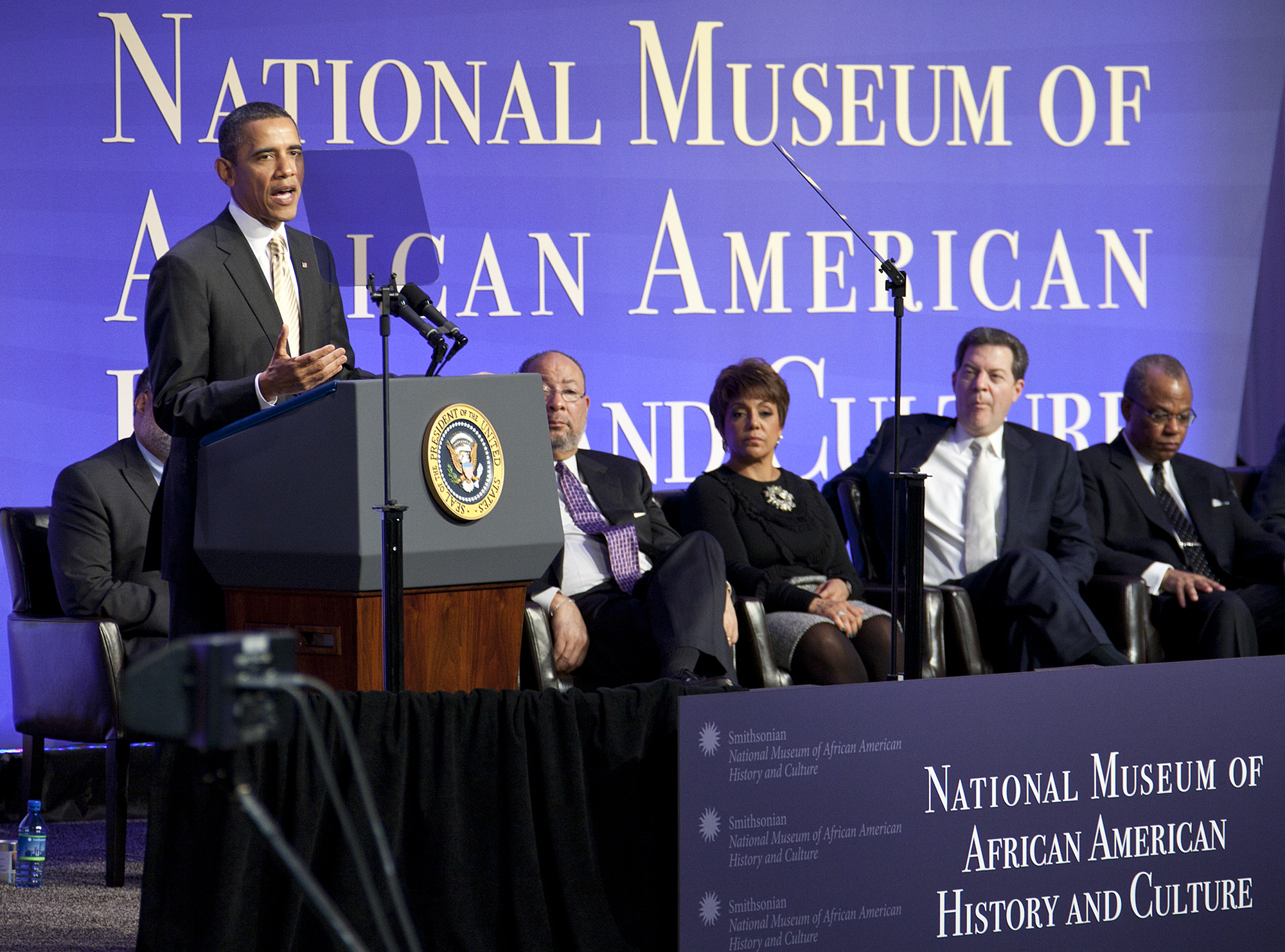 President Barack Obama speaks at podium in front of National Museum of African American History and Culture