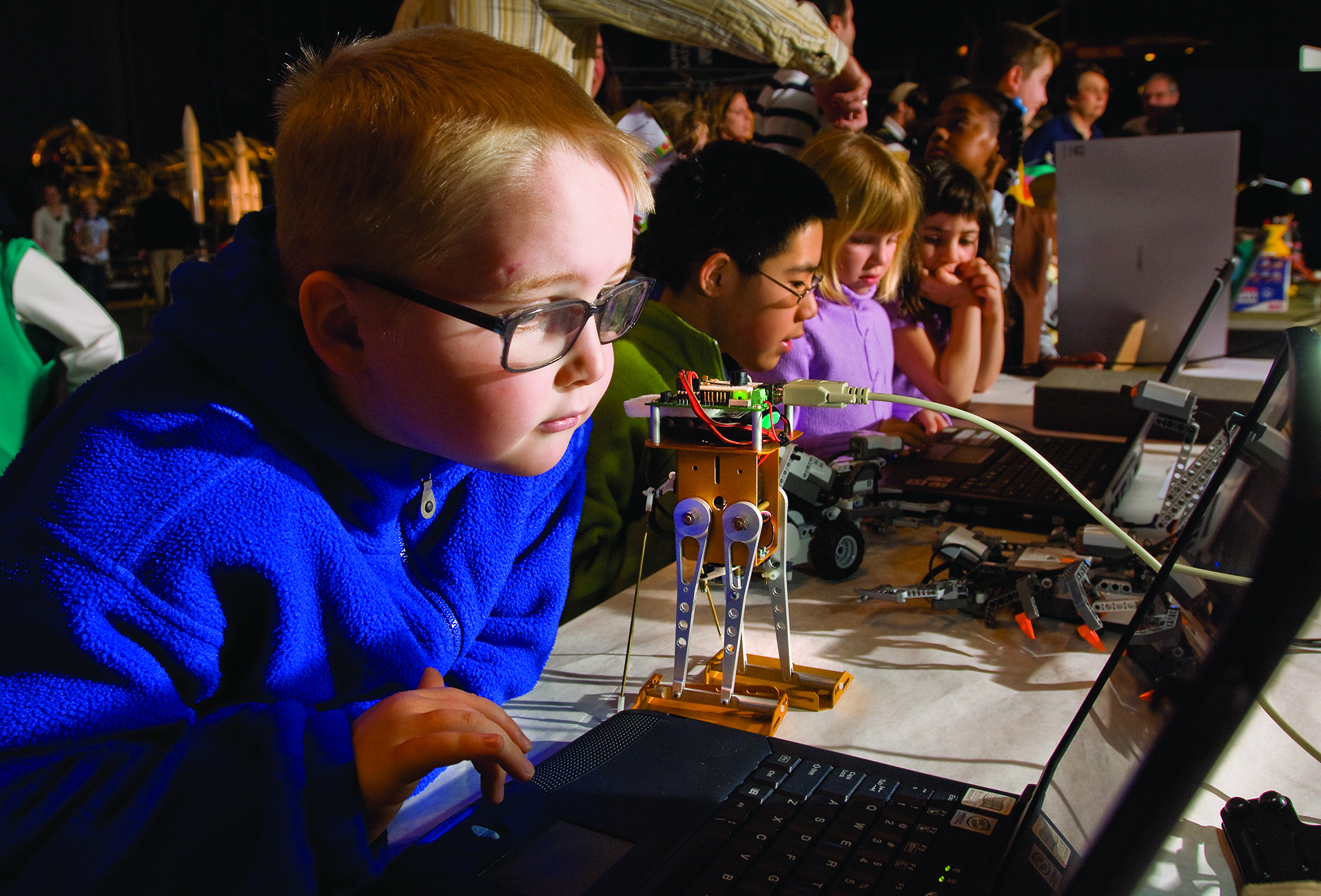 Young boy stares at computer screen among a large group of people