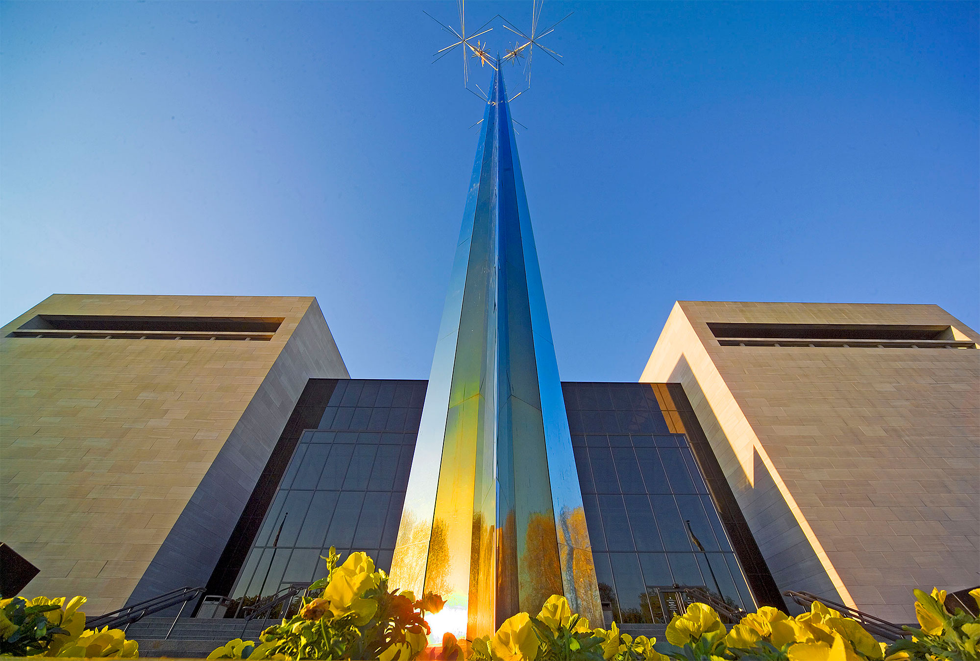Conical sculpture reflects early morning light in front of National Air and Space Museum building