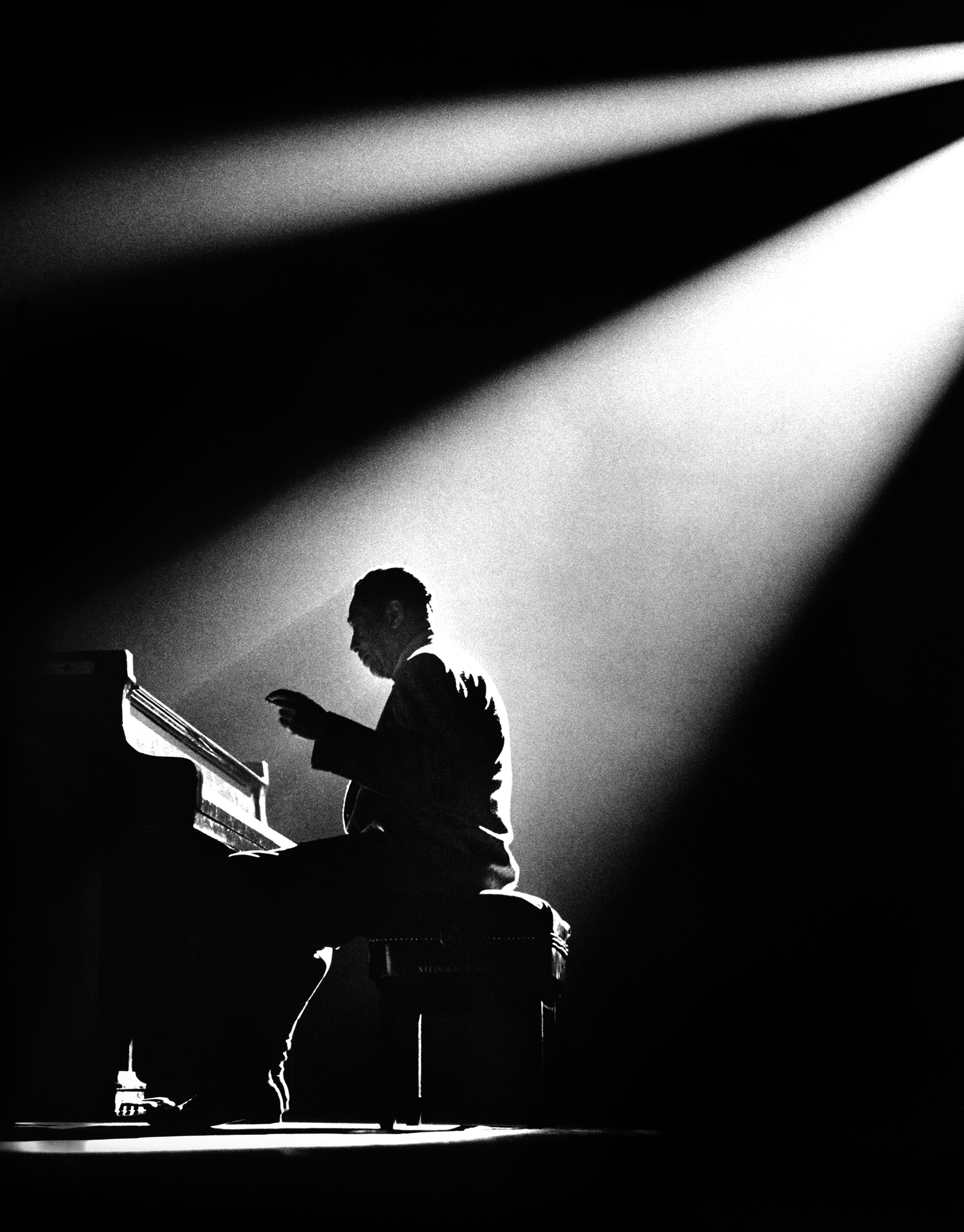 Black and white photo of pianist in silhouette