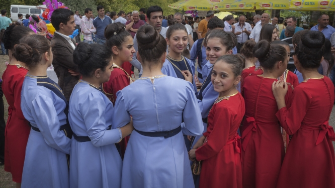 Costumed girls gather before a dance, one smiles at camera