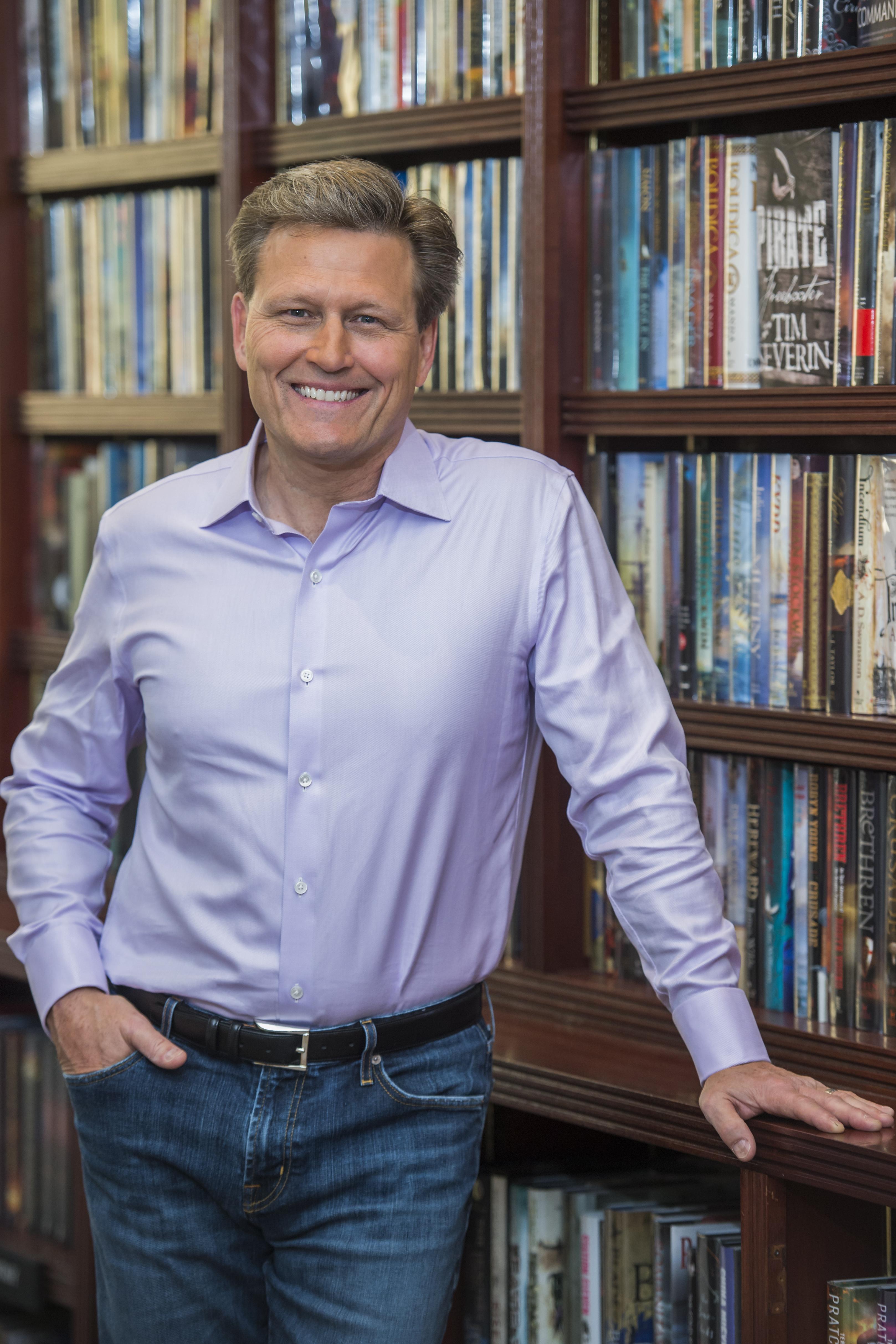 David Baldacci leans against bookcase