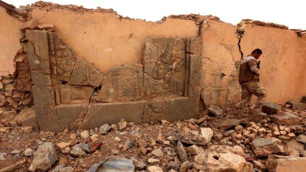An Iraqi soldier walks past damaged Assyrian frieze in Nimrud