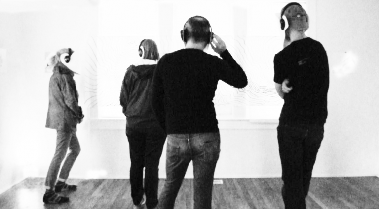 Group of people standing around with headphones on