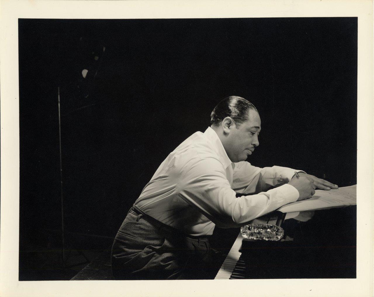 Duke Ellington in profile leaning over a piano