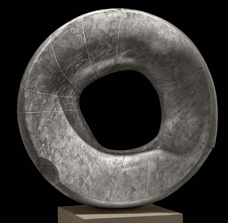 Sculpture of circular stone disc with hole in the middle