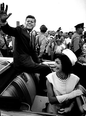 JFK waving from open convertible