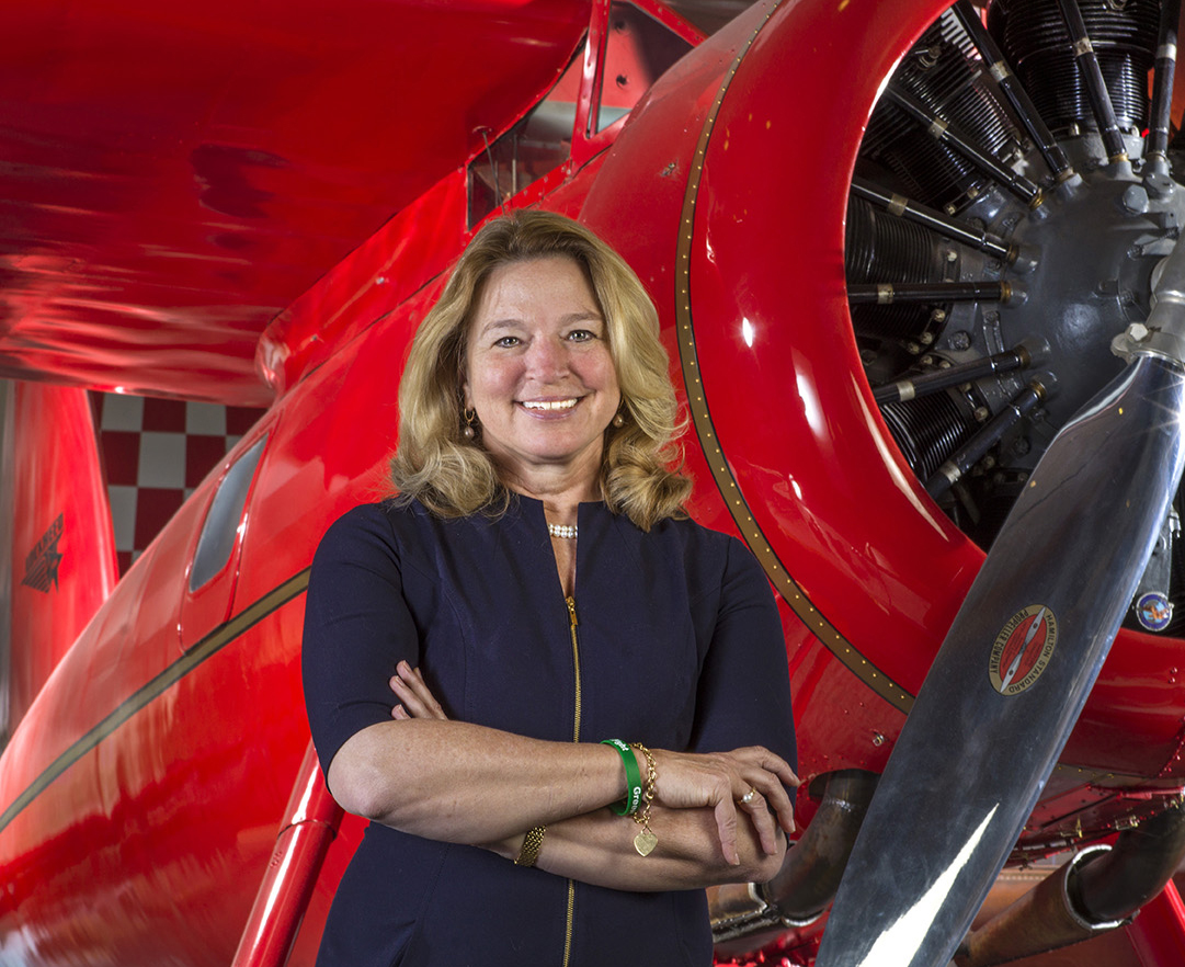 Ellen Stofan smiles with her arms crossed in front of an airplane
