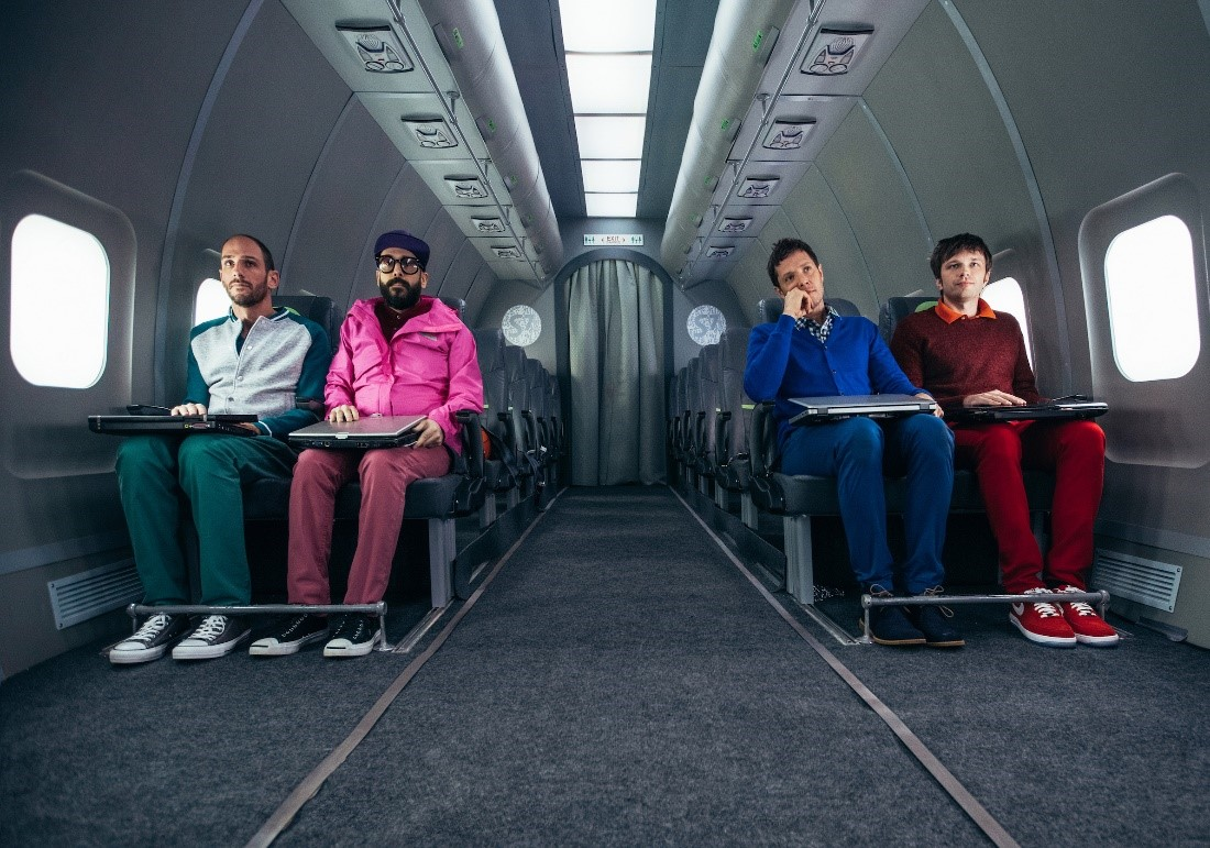 Four OK Go band members sitting in airplane seats