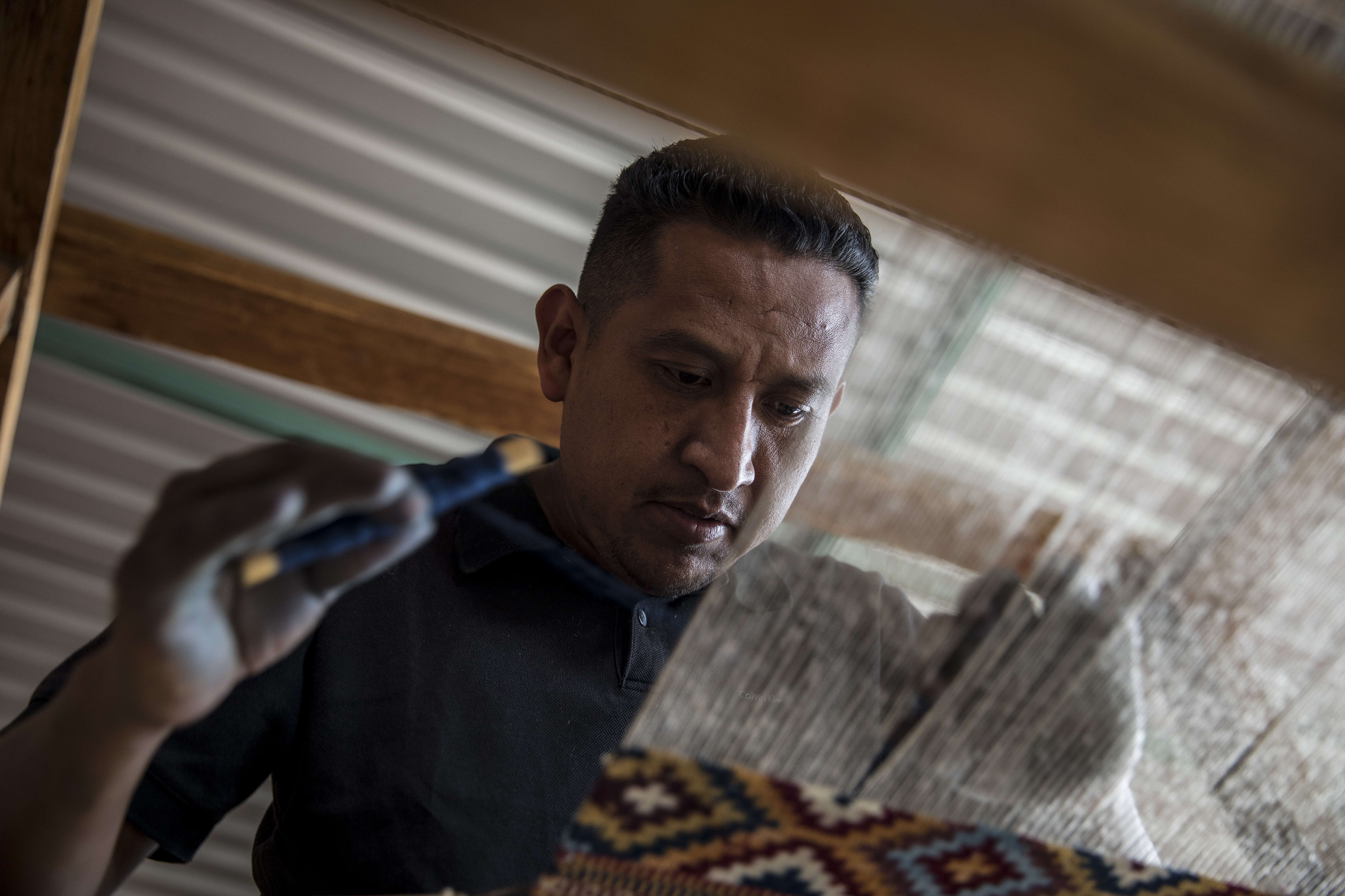 Man weaves a textile on a loom by hand