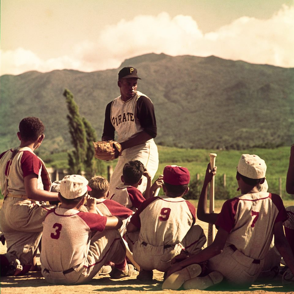 Man in baseball uniform stands above a group of young children whose backs are to the viewer