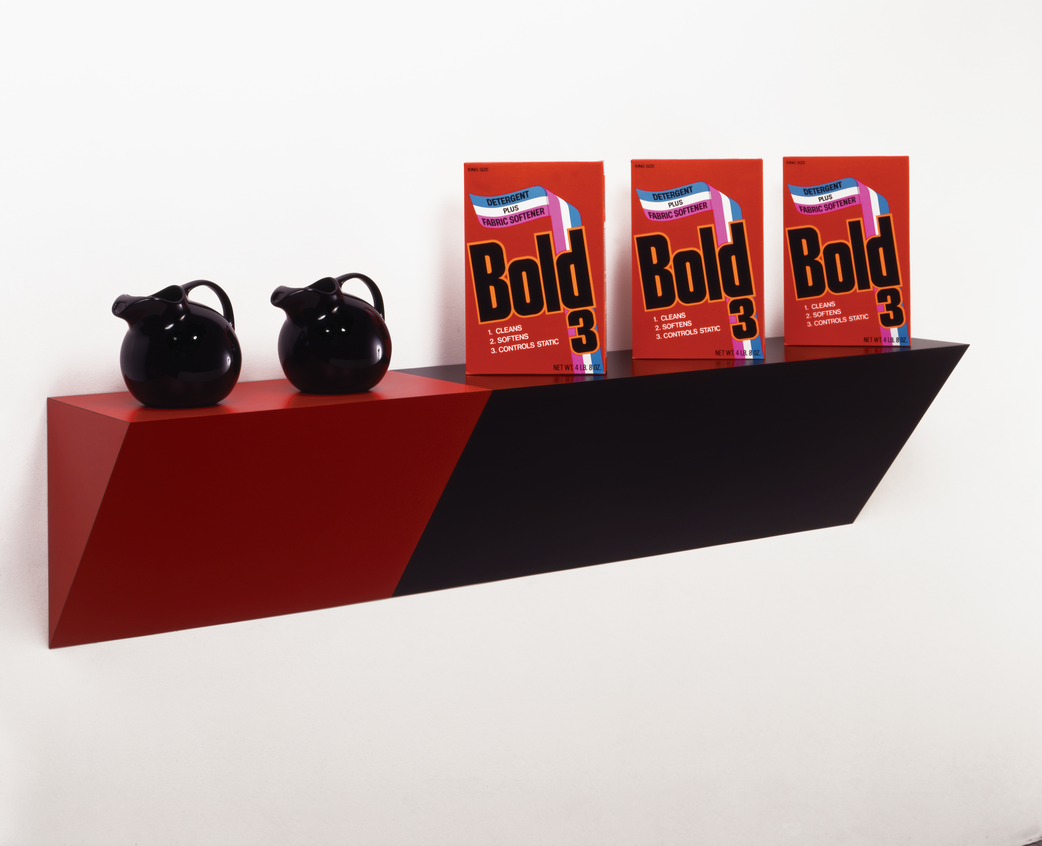red and black sculpture featuring detergent boxes and pitchers