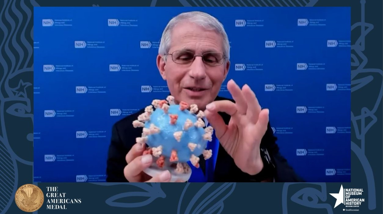 Dr. Fauci holds sculpture of a virus between his hands