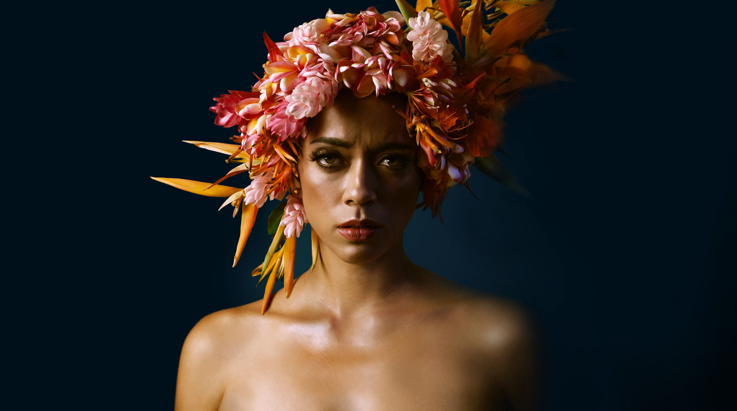 Woman with bare shoulders and floral headgear stares straight ahead