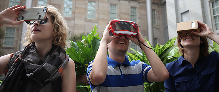 Three people using virtual reality viewers