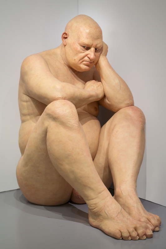 Big Man sculpture (overweight bald man sitting with head on hand)