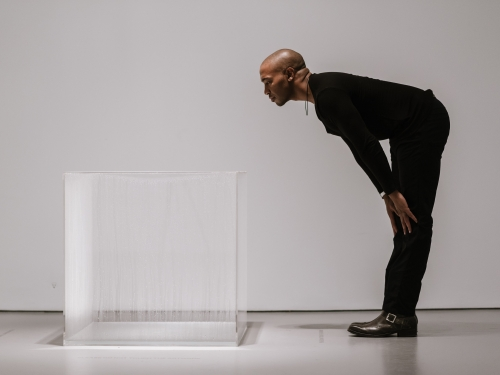 Man leaning over to look at a clear cube