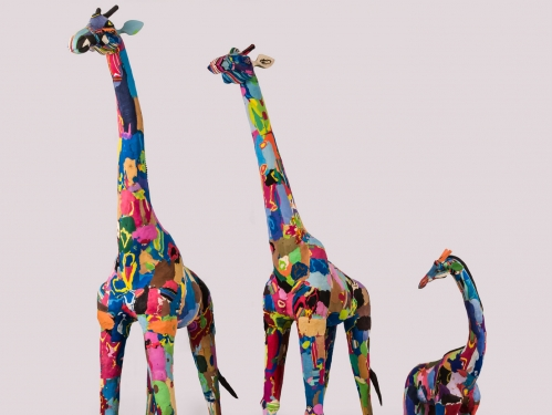 Three giraffe sculptures in many bright colors