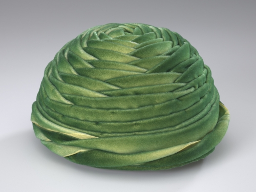 Green velveteen hat. It is circular with layers of fabric in a wrapped design.