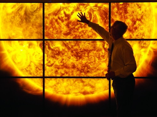 Man hold up hand to a series of large screens displaying the sun