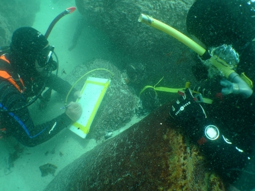 Two scuba divers underwater with sunken artifacts