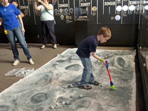 Child playing on model of moon's surface