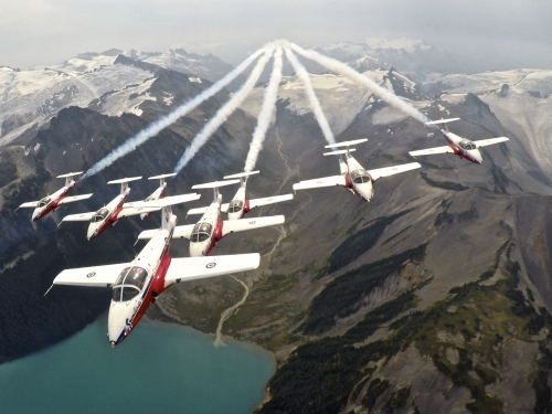 Canadian military planes in formation over mountains