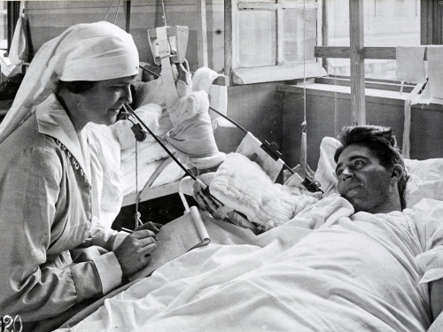 Nurse writing a letter for wounded soldier