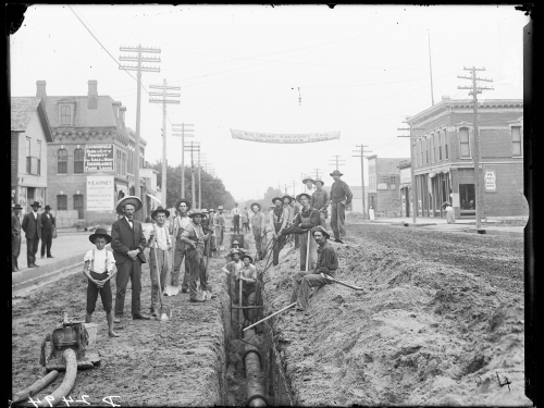 Black and white photo of workers installing sewer pipe