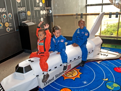 Children playing on model of space shuttle