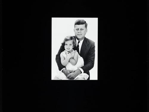 Black and white photo of JFK holding young Caroline