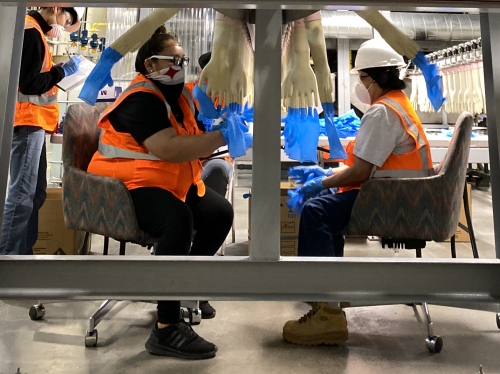 Two people sit while working in a factory setting.