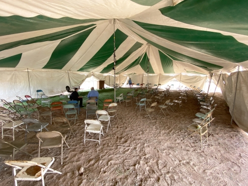 Empty chairs underneath a large outdoor tent