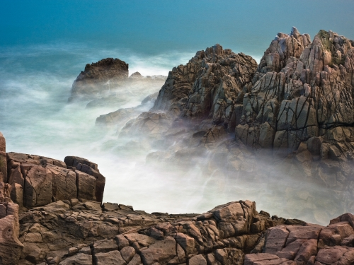 Mists rising from ocean between large rock faces