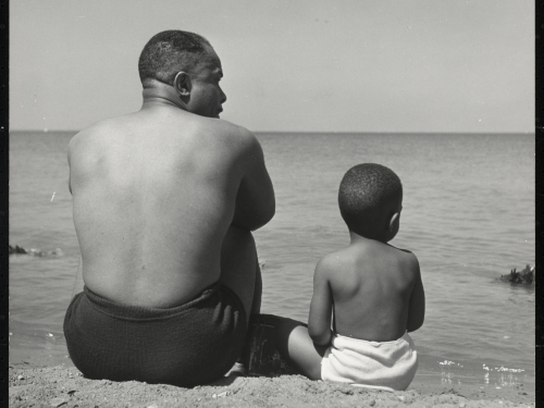 Father and young son on beach with backs to the camera