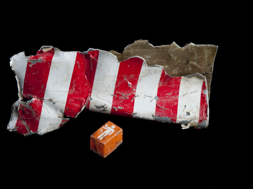 Fragment of red-striped wreckage and orange call button