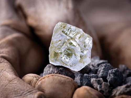 Uncut diamond held in dirty hand