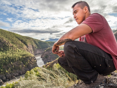 still image of squatting man overlooking a river