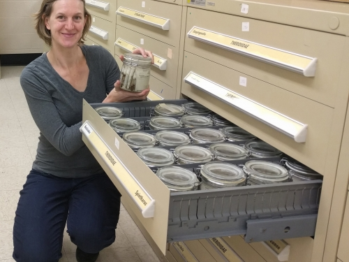 Researcher Hannah Wood holds jar with specimens