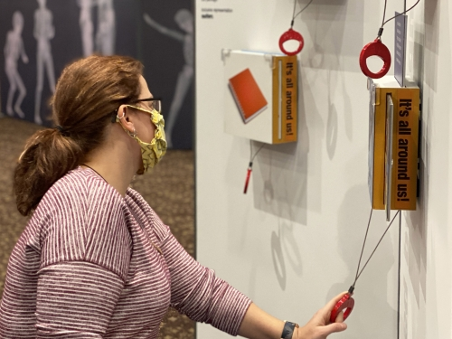 Woman interacts with items on a gallery wall