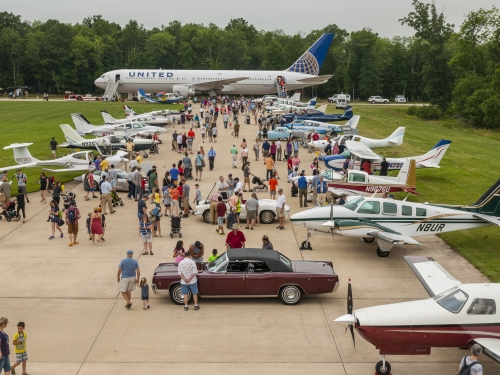 Visitors look at airplanes parked on runway