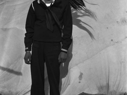 Young man in Navy uniform wearing headdress