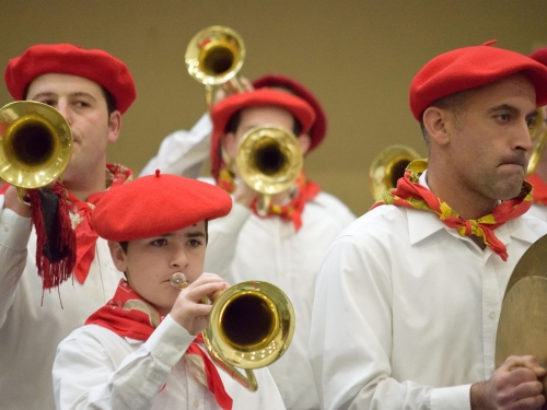 Boys and men wearing red berets and plating trumpets
