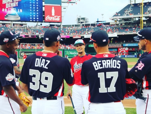 Four baseball players with their backs to the viewer talk to another player facing the camera in a baseball stadium