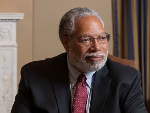 Lonnie Bunch looks away while sitting at a table with an open notebook in front of him