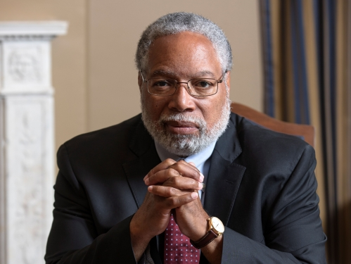 Lonnie Bunch sits at table with hands folded under chin